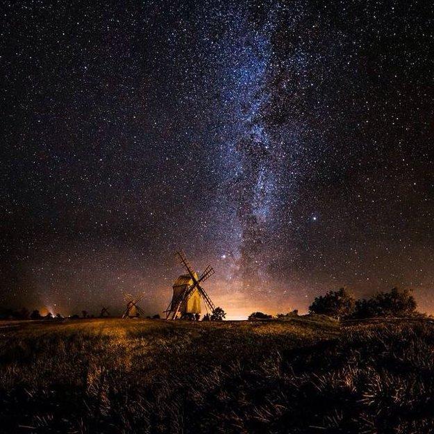 Mliečna cesta stúpajúca spoza starých veterných mlynov v švédskom meste Resmo.