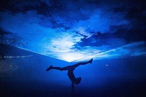 Návštevníčka tancuje pri svetelnej inštalácii počas druhého dňa hudobného festivalu.