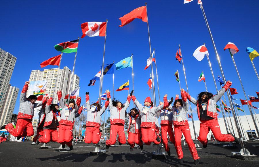 Skupina doborvoľníkov skáče pred vztýčenými vlajkami na konci slávnostného otvorenia olympijskej dediny v Kangnungu.