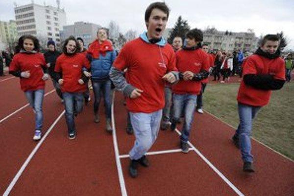 Študenti bežia prvé čestné kolečko počas slávnostného otvorenia atletického štadióna.