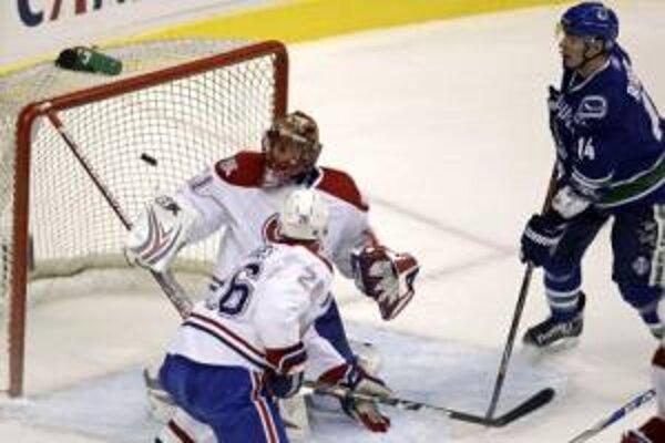 Slovenský brankár Jaroslav Halák (vľavo) z Montrealu Canadiens dostáva gól po strele Daniela Sedina.