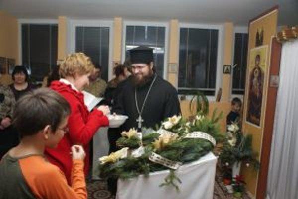 Jerej Marek rozdáva posvätený chlieb v predvečer sviatku.