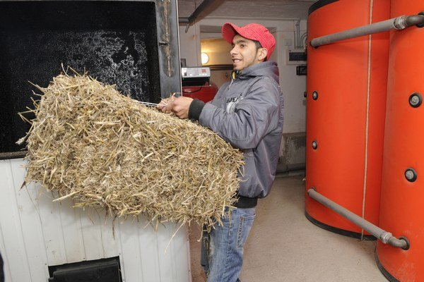 Marián Pirko Puľo prikladá do nového kotla na biomasu. Sociálny program s rómskou komunitou v areáli Malinka realizuje združenie Svatobor už ôsmy rok.