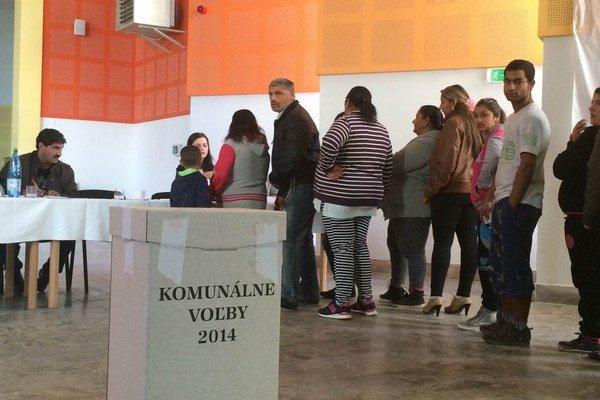 Rómovia z Jarovníc stoja v rade vo volebnej miestnosti počas sobotňajších volieb.
