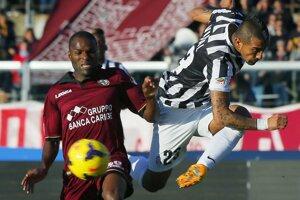 Futbalistu Juventusu Artura Vidala (vpravo) sa o loptu snaží obrať hráč Livorna Innocent Emenghara.