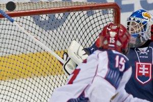 Brankár slovenskej reprezentácie Ján Kožiak sa vrchnou časťou hokejky snaží vytesniť letiaci puk.
