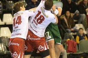 Hráč Tatrana Prešov Lukáš Urban (v zelenom) sa pokúša pod tlakom súpera prihrať loptu.