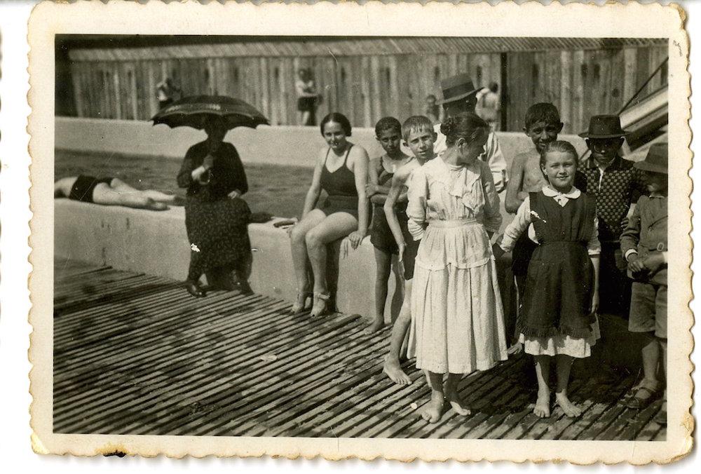 Nedeľná fotografia pri bazéne Ilona. Dievča v bielych šatách je dcérou richtára zo Starého Hrádku. Vľavo so slnečníkom pravdepodobne jej stará mama alebo opatrovateľka.