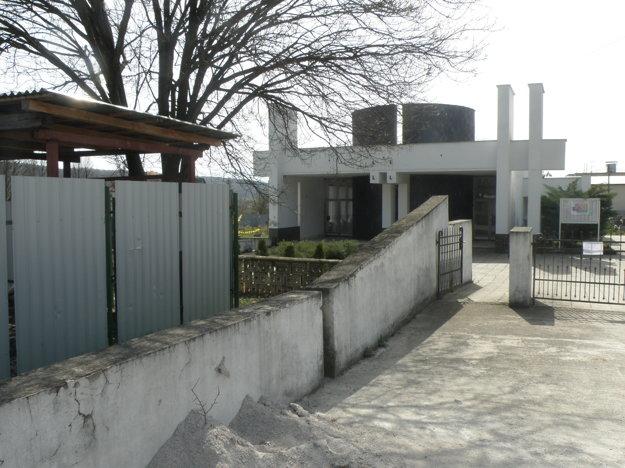 V pozadí je dom smútku, vpredu zberný dvor, ktorý už oplotili.