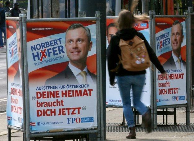 Žena prechádza okolo pútačov s tvárou kandidáta slobodných Norberta Hofera.