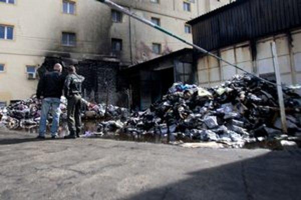 Požiar vznikol pri smetných nádobách pod žltou bytovkou. Rozšíril sa na sklad - vpravo. Na zemi sú tisícky kusov zničeného oblečenia.