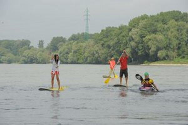 Vodáci z areálu Divokej Vody v Čunove na Dunaji na rafte, kajaku a stand up paddle – surfových doskách, ktoré sa ovládajú postojačky s pádlom.