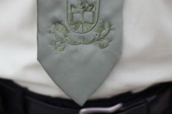 Detail slávnostnej kravaty. Je na ňom aplikácia obecného erbu a rastlinný ornament.