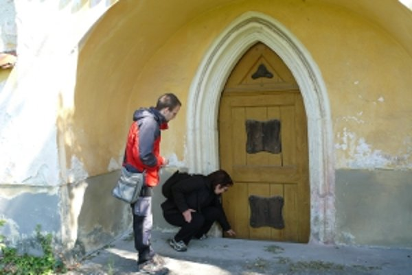 Katarína Machatová ukazuje, o koľko kostol klesol.