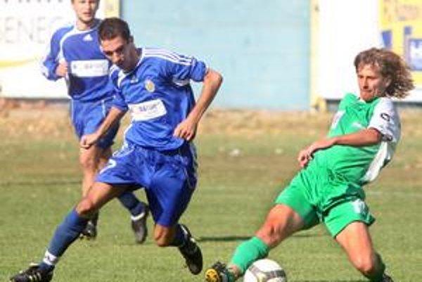 Pezinčan Štefan Maťaš (v zelenom) v súboji s Ružinovčanom Dušanom Vangelom (v modrom) v zápase 7. kola III. futbalovej ligy FC Ružinov – PŠC Pezinok 1:1.