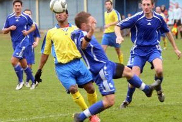 Brazílčan Carlos Ferreira z tímu Ružinova (v žltom) sa v zhustenej obrane Slovenského Grobu nepresadil. Zo zápasu 10. kola III. futbalovej ligy  FC Ružinov – Slovenský Grob 0:1.