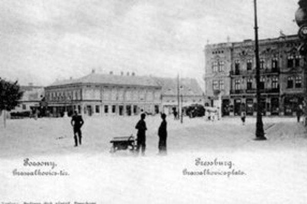 Ďalší pohľad na voľakedajšie Grassalkovichovo (Hodžovo) námestie. Dvojposchodový dom bol posledný objekt stojaci na Palisádach. Zbúrali ho pri rozširovaní námestia, rovnako ako jednoposchodový dom v pozadí. Medzi nimi stála do konca 18. storočia mests
