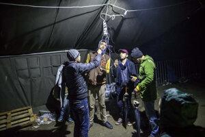 Utečenci si nabíjajú telefóny.