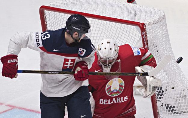 Bieloruský brankár Vitalij Kovaľ vyráža puk pred cloniacim Tomášom Jurčom.