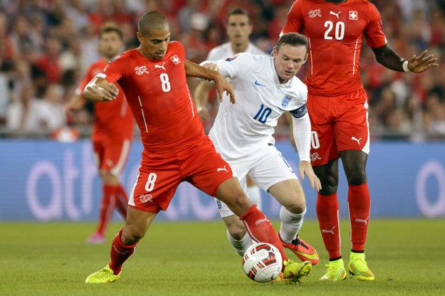 Gökhan Inler (s číslom 8) je aj bývalým kapitánom Švajčiarska. Na snímke bojuje o loptu s hráčom Anglicka Waynom Rooneym.