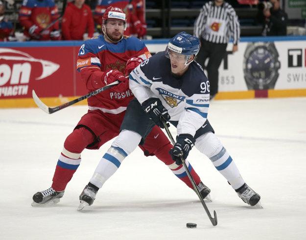 Ruský hráč Roman Ljubimov (vľavo) a hráč Fínska Mikko Rantanen v súboji o puk.