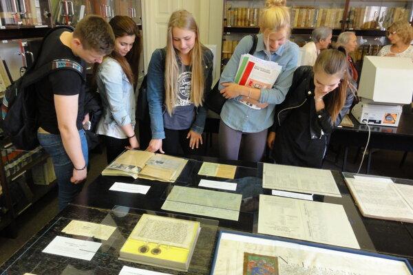 Študenti si prezerajú najstaršie dokumenty, aké v archíve majú.