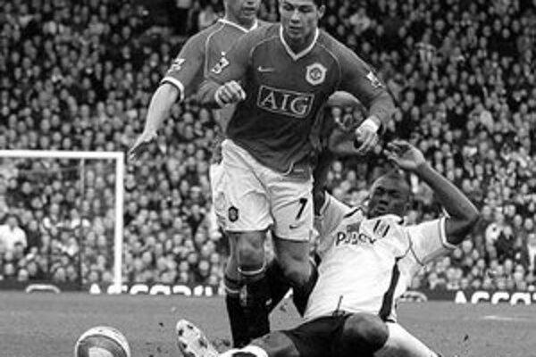 Philipp Christanval z Fulhamu (na trávniku) sa snaží zastaviť Cristiana Ronalda (7). Manchester United vyhral na ihrisku súpera 2:1.