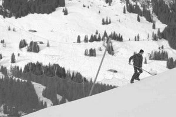 Vojak švajčiarskej armády rozhadzuje sneh na Lauberhorne. Mal sa na ňom jazdiť už včerajší tréning, ale dážď a teplé počasie lyžiarov na svah nepustili.