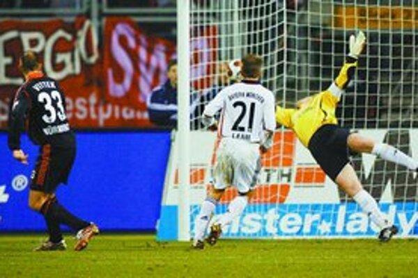 Brankár Bayernu Oliver Kahn (vpravo) neúspešne zasahuje pri treťom góle do svojej brány z kopačky slovenského hráča Norimbergu Róberta Vitteka (vľavo) .
