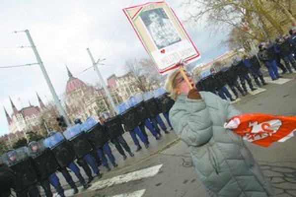 """Protivládna demonštrantka v Budapešti. Na tabuli má Orbánovu fotku, srdiečko a nápis """"Vydrž. Viktor, sme s tebou."""""""