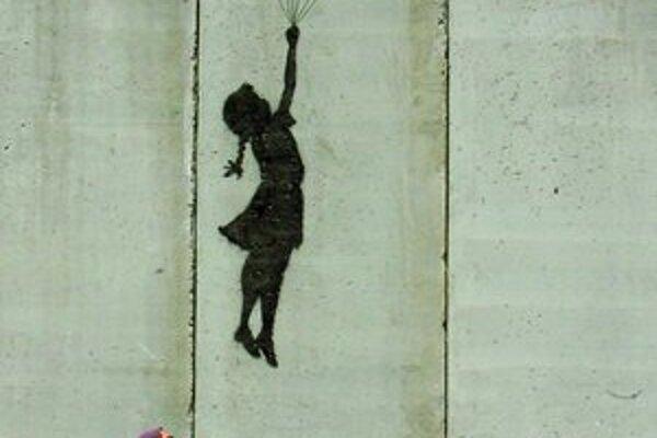Palestínska žena s dieťaťom kráča okolo diela jedného z najznámejších streetartistov Banksyho namaľovanom na izraelskom múre pri meste Aram.
