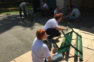 Dobrovoľníci natierajú lavičky v žilinskom Zariadení pre seniorov.