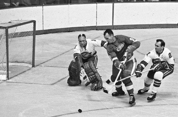 Na snímke z 26. októbra 1967 sa Gordie Howe (v strede) pokúša pretlačiť puk za chrbát brankára Californie Seals Charlieho Hodgea.