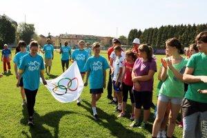 Mladí športovci prinášajú olympijskú vlajku.