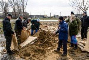 Dobrovoľníci plnia vrecia s pieskom na zvýšenie hrádze.
