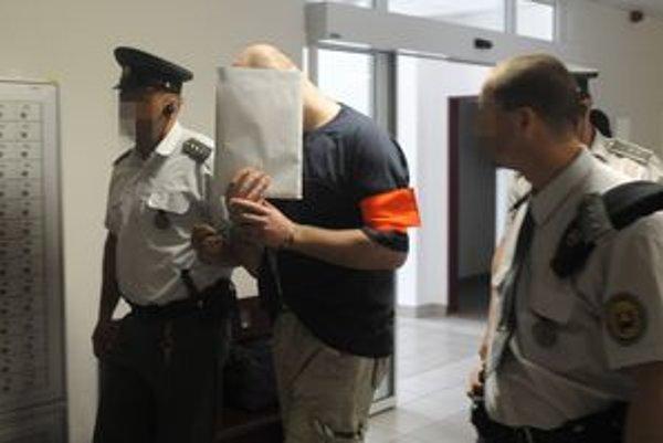 Páchateľa privádzajú na súdne pojednávanie. Foto: TASR