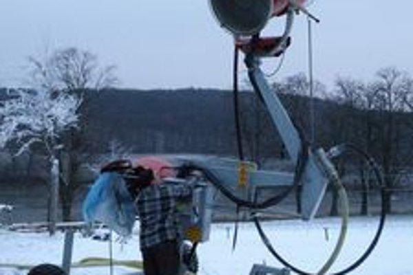 Pracovník obce pri obsluhe snehového dela v stredu ráno.