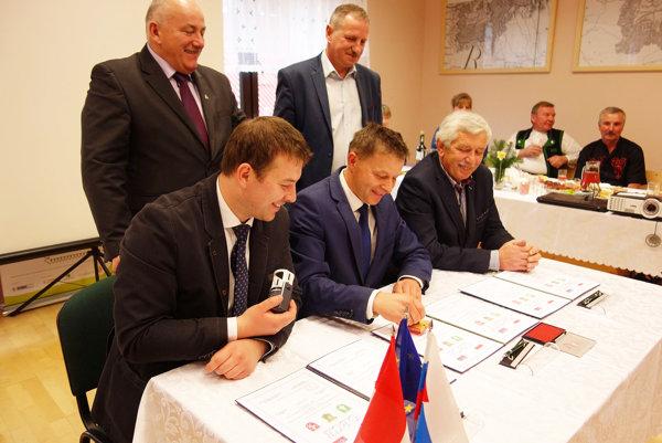 Starosta Marek Majdiš (vľavo), wójt gminy Ujsoly Tadeusz Pietka (v strede) astarosta Milan Vrábeľ podpisujú trojstrannú dohodu.