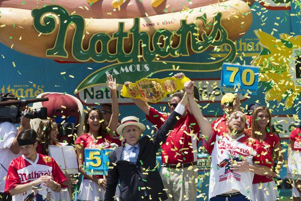 """Dlhoročný šampión Joey """"Jaws"""" Chestnut (vpravo) v tradičnej súťaži v jedení hotdogov za desať minút zjedol 70 párkov v rožku."""