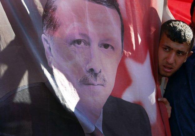 Muž sa pozerá na podobizeň prezidenta Erdogana.