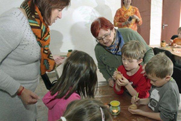 Ľudmila Bátorová (v strede) sleduje deti ako zdobia vajíčka roztopeným voskom.
