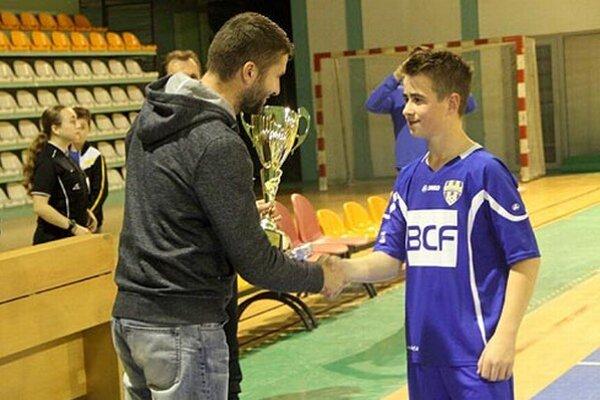 Erik Krčmár z Nevidzian preberá víťazný pohár z rúk Ladislava Prešinského, člena Výkonného výboru ObFZ v Nitre.