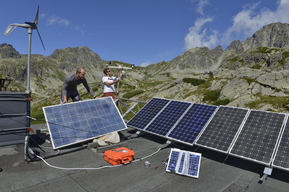 Meteorológ Miroslav Žiak drží poškodený solárny panel. Vľavo je vrtuľa pred demontážou.