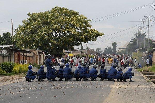 Policajti sa bránia pred kameňmi, ktoré hádžu demonštranti počas nepokojov v burundskej metropole Bujumbura 28. apríla 2015.