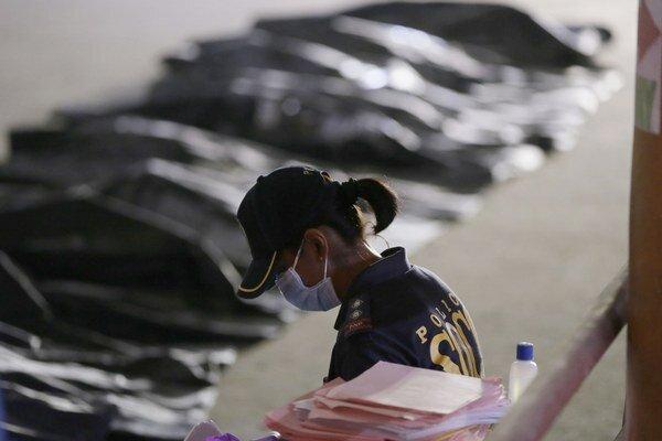 Príslušníčka polície skúma pozostatky obetí.