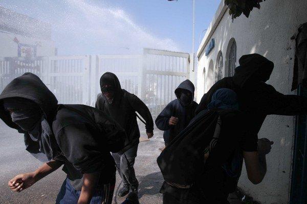 Protestujúci utekajú pred vodným delom, ktoré polícia použila pri univerzite v Santiagu.