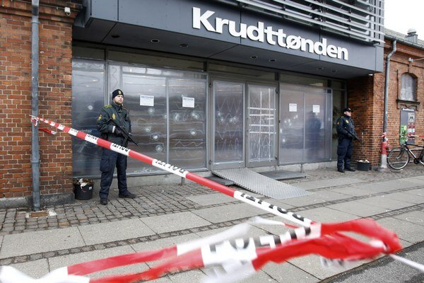 Policajt hliadkuje pred rozstrieľanými výkladmi kaviarne v Kodani.