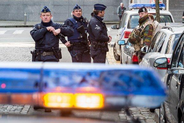 Belgickí policajti a ochrankár stoja pred budovou Európskeho parlamentu v Bruseli po zásahu proti Slovákovi.