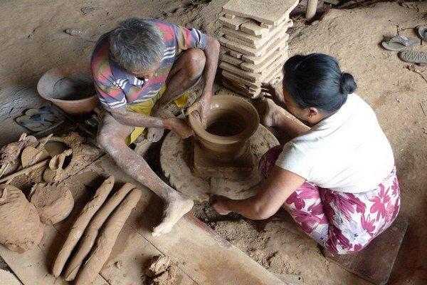 Pri kruhu sedí staršia dvojica. Nakladajú hlinu a tvarujú nádobu za nádobou.