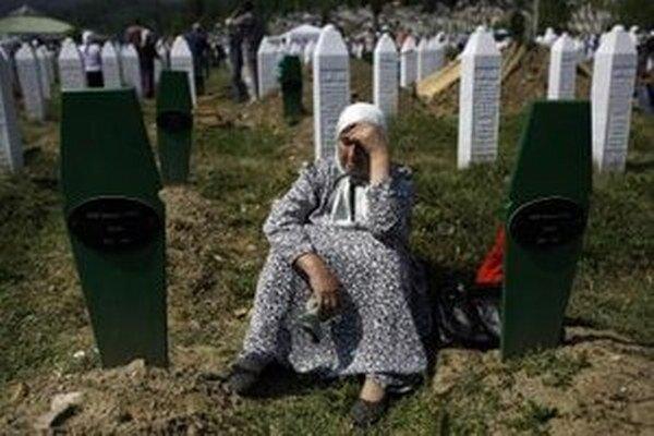 Žena smúti pri hroboch svojich synov na cintoríne v Potočari blízko Srebrenice.